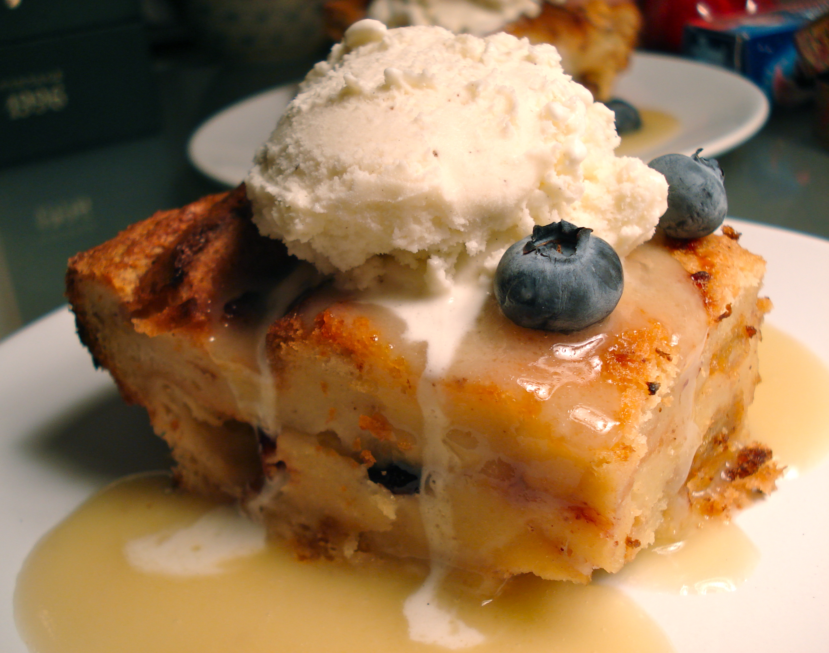 blueberry bread pudding with vanilla ice cream and maple bourbon sauce